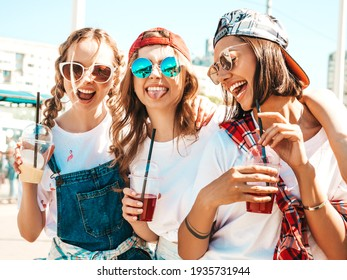 Three young beautiful smiling hipster female in trendy summer clothes.Sexy carefree women posing outdoors.Positive models holding and drinking fresh cocktail smoothie drink in plastic cup with straw - Shutterstock ID 1935731944