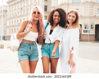 Three young beautiful smiling hipster female in trendy summer clothes.Sexy carefree multiracial women posing on the street background.Positive models having fun in sunglasses. Cheerful and happy - Shutterstock ID 2021165189
