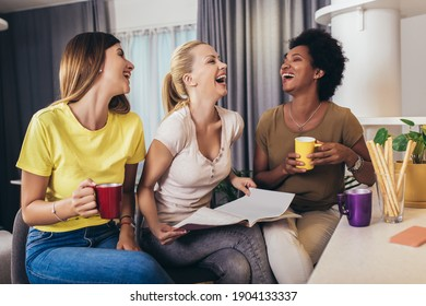 Three young beautiful smiling women reading magazine at home.