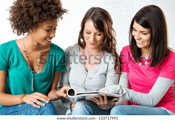 Three Young Beautiful Smiling Women Reading Magazine