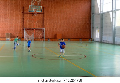 Three young boys playing ball on a bright indoor court lit by daylight through large windows