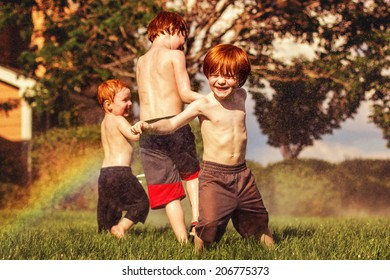 Three young brothers playing in the sprinklers on a hot day -- image taken outdoors in Reno, Nevada, USA