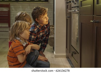 three young brothers watching cookie bake in oven
