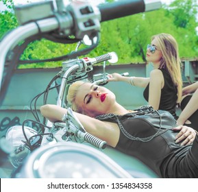 Three Young brutal cute girl lie on chopper and wear black leather dress and stylish sunglasses. Empty space for inscription.3 Biker Woman on motorcycle against metal bridge background.Blond female