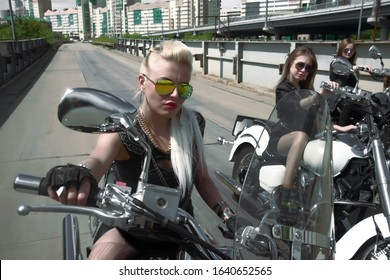 Three Young brutal cute girl lie on chopper bike and wear black leather dress and stylish sunglasses.Empty space for inscription 3 Biker Woman on motorcycle on iron bridge background. Blonde female