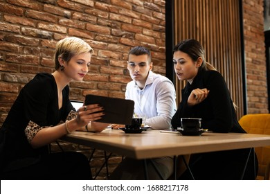 Three young business colleagues having a meeting in a modern cafe in the late evening hours. Successfull startup team brainstorming after work hours.
