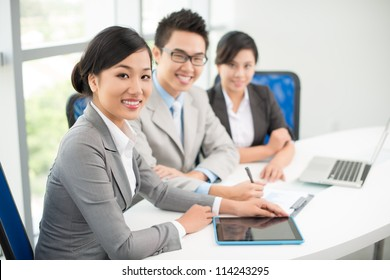 Three young business colleagues sitting in office during meeting