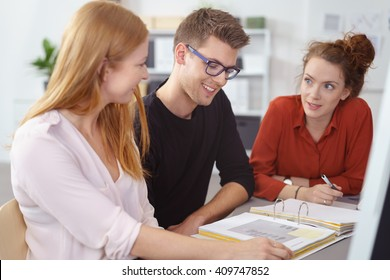 Three young business entrepreneurs at work sitting together at a desk discussing notes in a large office binder with focus to the young man in the center