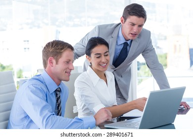 Three young business people using laptop in office