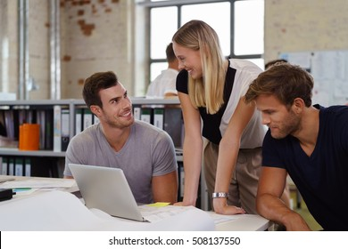 Three young business people working as a team gathered around a laptop computer reading the information on the screen in an open plan modern office