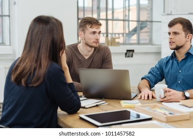 Three young businesspeople in a meeting sitting around a table with paperwork and digital devices having a discussion