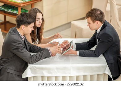Three young businesspeople sitting in a meeting at the table and working on the tablet. Top view of the three confident and successful businessmen.