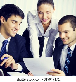Three young businesspeople working with document at office, teamwork concept