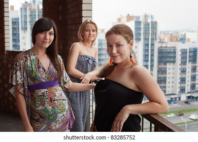 Three young Caucasian women standing on balcony of city high-rise building