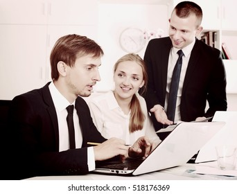 Three young cheerful coworkers working on document paper together in firm office