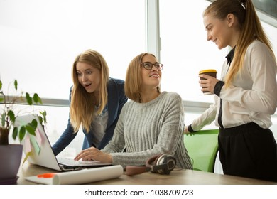Three young cheerful female business colleagues working together at the modern office discussing work using laptop preparing startup project at the workplace.