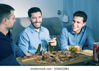 Three young cheerful men talking and laughing while enjoying beer and pizza at home