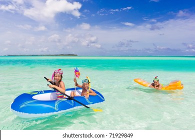 Three young children playing on lilo and dinghy in tropical sea with blue sky and cloudscape background.
