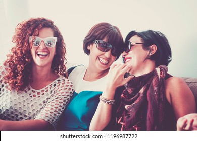 three young crazy females friends having a lot of fun at home on the sofa. all of them with sunglasses and laughi and smiles. close contact for best friendship. joy and people smiling, vintage colors