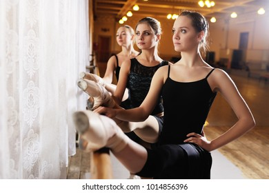 three young cute ballerinas perform exercises on a choreographic machine or barre on the background of a ballet class