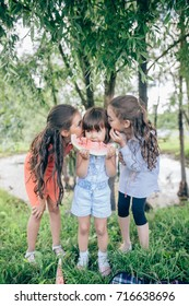 Three young cute funny girls eating watermelon and making funny faces over park outdoor