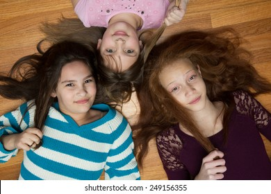 Three young, diverse  girls  lying on a wood floor looking up at the camera. One African American with red hair, one hispanic and one caucasian