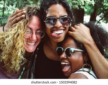Three young diverse women smiling and enjoying life.