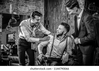 Three young elegant positive friends pose in interior of barbershop. Black-white photo.