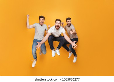Three young excited men jumping together isolated over yellow background