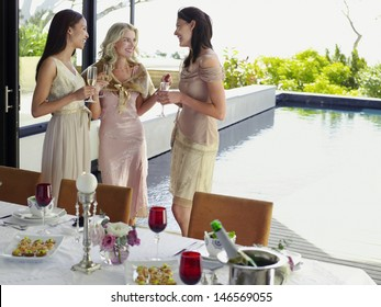 Three young female friends with champagne flutes at dinner party