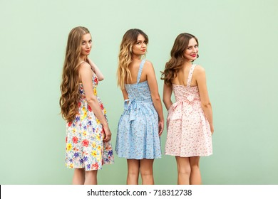 Three young female friends in cute dresses turned over the shoulder, toothy smile and looking at camera. Young adult women standing back in front of green background, posing and smiling.