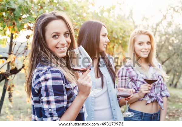 Three young female friends drinking wine in vineyard at sunset
