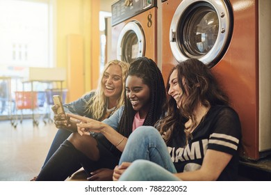 Three young female friends laughing and sitting together on a laundromat floor using a cellphone