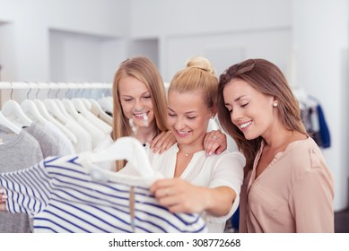 Three Young Female Friends Looking at the Quality of a Shirt with Happy Facial Expressions Inside a Clothing Store.