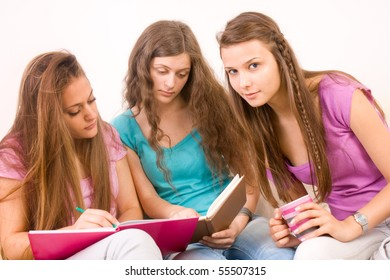 Three young female friends sitting in the living room and looking at books