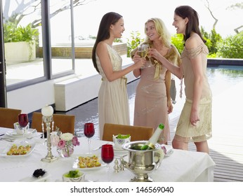 Three young female friends toasting champagne flutes at dinner party