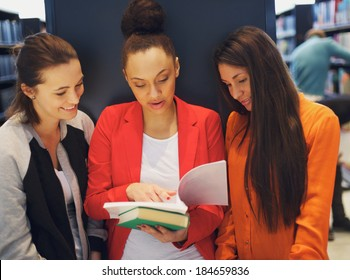 Three young female students standing in the library and looking at a book together. University students reading reference books for their studies.