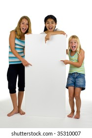three young females point at something on a white board