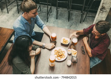Three Young Friends Drinking Beer in Bar