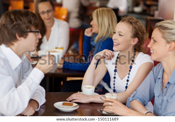 Three young friends having coffee together in a cafe seated around a small table chatting and smiling