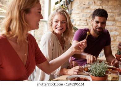 Three young friends having fun eating tapas at a restaurant