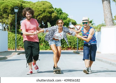 Three young friends having fun with a skateboard