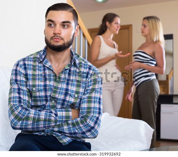 Three young friends having misunderstanding at domestic interior