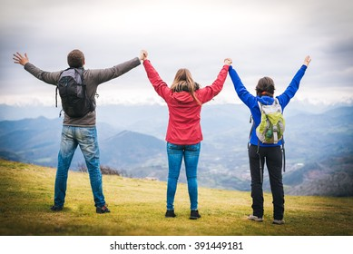 three young friends hiking outdoor rising arms holding hands backwards. successful team reaching the sumit.