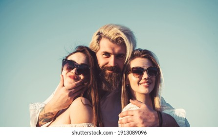 Three young friends, man smiling with two girls are enjoying summer vacation.
