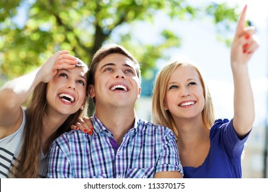 Three young friends pointing