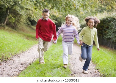 Three young friends running on a path outdoors smiling