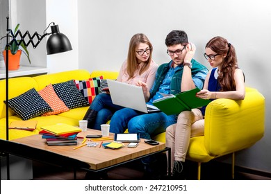 Three young friends or students reading colorful books on the yellow couch at home