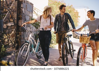 Three young friends walking together having fun. Young people with bikes walking outdoors in city.