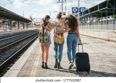 Three young friends women at the station walking and waiting train for their trip in summer with face mask for protection by infection from Coronavirus, Covid-19 - Millennials having fun together